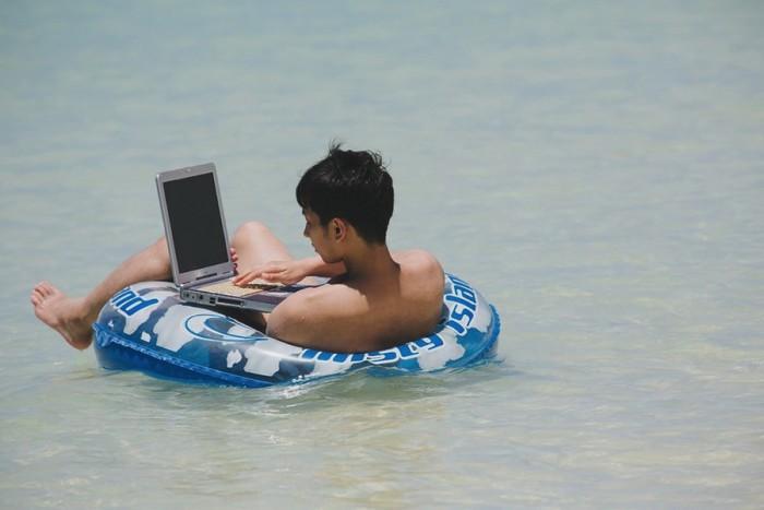 浮き輪の上で作業をする男性