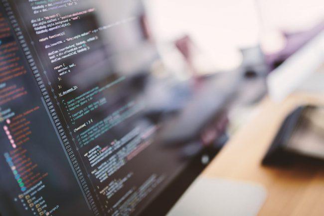 プログラムコードが表示されたパソコン